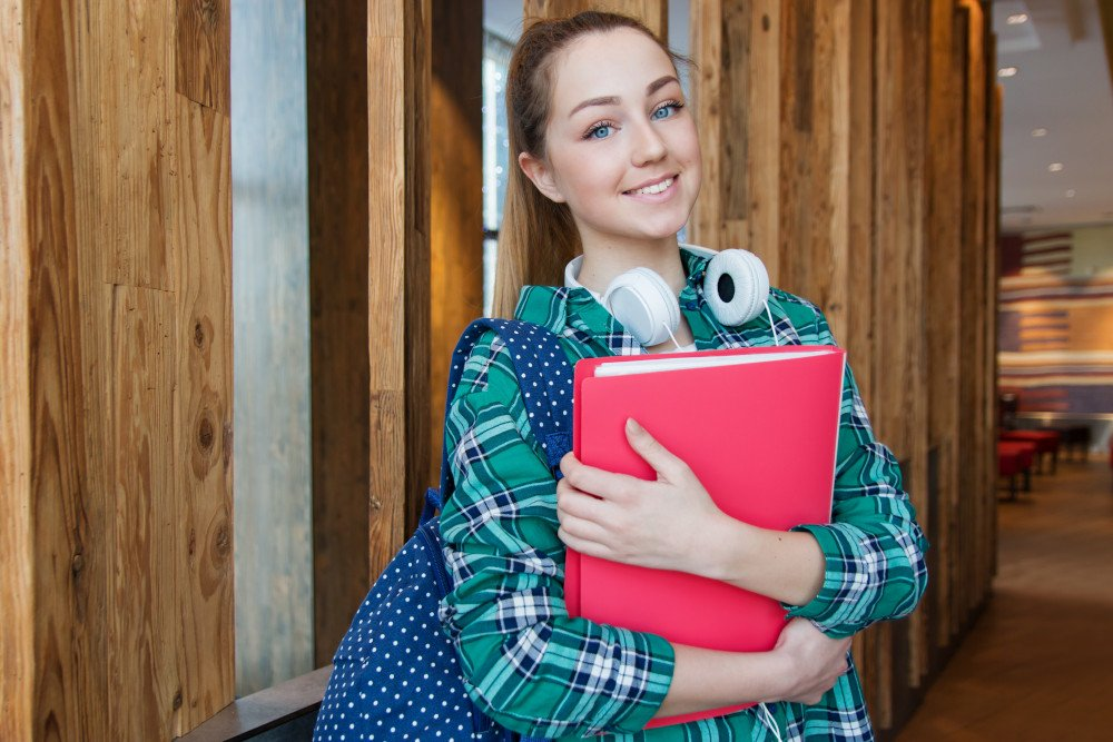 female student smiling with folder in her arms
