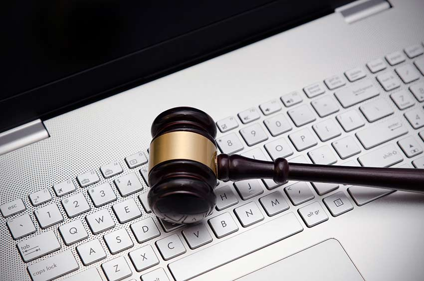 A judge's gavel lying on a white keyboard
