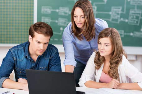 Woman looks at laptop with two youngsters at her side and a blackboard behind her.