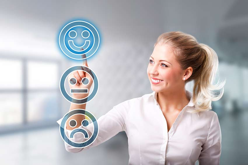 A smiling woman touching a smiley face icon on a touch screen
